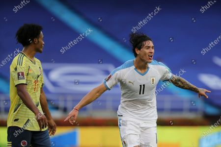 Uruguay's Darwin Nunez runs past Colombia's Juan Cuadrado celebrating after scoring his side's third goal during a qualifying soccer match for the FIFA World Cup Qatar 2022 at the Metropolitano stadium in Barranquilla, Colombia