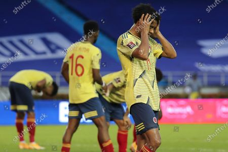 Colombia's Juan Cuadrado holds his head after his side's 0-3 lost against Uruguay in a qualifying soccer match for the FIFA World Cup Qatar 2022 at the Metropolitano stadium in Barranquilla, Colombia