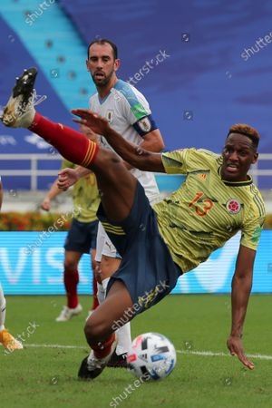Uruguay's Diego Godin, back, eyes the ball after Colombia's Yerry Mina missed a shot during a qualifying soccer match for the FIFA World Cup Qatar 2022 at the Metropolitano stadium in Barranquilla, Colombia
