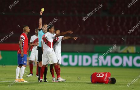 Referee Esteban Ostojich, second right, shows the yellow card to Peru's Renato Tapia, center, during a qualifying soccer match against Chile for the FIFA World Cup Qatar 2022 in Santiago, Chile