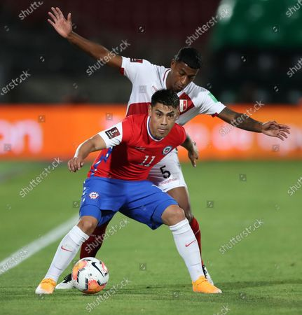 Chile's Felipe Mora, front, and Peru's Miguel Araujo battle for the ball during a qualifying soccer match for the FIFA World Cup Qatar 2022 in Santiago, Chile