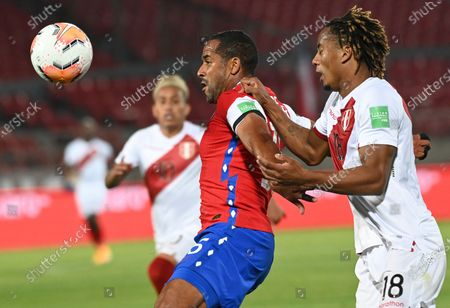 Chile's Jean Beausejour, left, and Peru's André Carrillo battle for the ball during a qualifying soccer match for the FIFA World Cup Qatar 2022 in Santiago, Chile