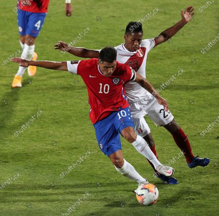 Chile's Cesar Pinares, left, and Peru's Pedro Aquino battle for the ball during a qualifying soccer match for the FIFA World Cup Qatar 2022 in Santiago, Chile