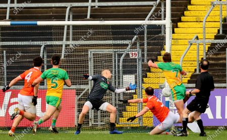 Donegal vs Armagh. Donegal's Peadar Mogan scores his sides first goal despite goalkeeper Blaine Hughes and Ryan Kennedy of Armagh