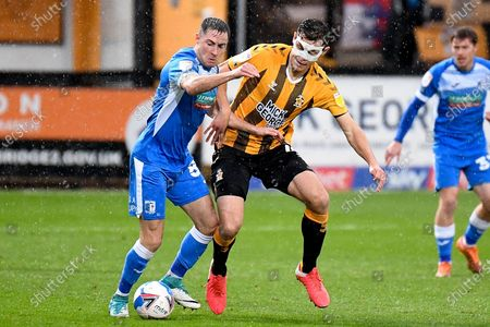Cambridge United midfielder Paul Digby (4) battles for possession  with Barrow AFC midfielder Mike Jones (8) during the EFL Sky Bet League 2 match between Cambridge United and Barrow at the Cambs Glass Stadium, Cambridge