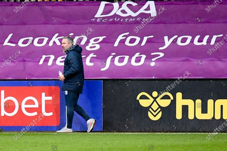 """Stock Image of Barrow AFC manager David Dunn  walks past a sign saying """"looking for your next job"""" during the EFL Sky Bet League 2 match between Cambridge United and Barrow at the Cambs Glass Stadium, Cambridge"""