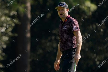 Justin Rose, of England, reacts to his putt on eh first hole during the third round of the Masters golf tournament, in Augusta, Ga