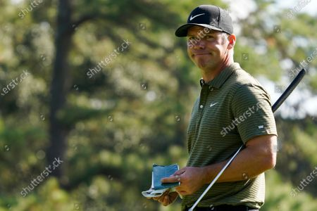 Paul Casey, of England, looks over his course notes after putting on the first green during the third round of the Masters golf tournament, in Augusta, Ga
