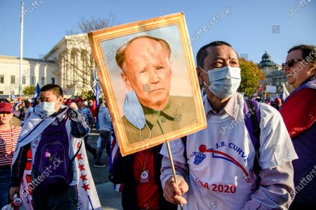 A Trump supporter holds a painting of Joe Biden resembling a portrait of Chinese Communist Revolutionary Mao Zedong as people gather near the Supreme Court for the 'Million MAGA March' on November 14, 2020 in Washington, DC.