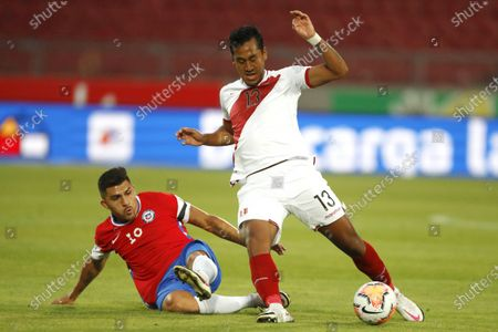 Cesar Pinares of Chile slides in on Renato Tapia of Peru; National Stadium of Santiago, Santiago, Chile; World Cup 2020 Football qualification, Chile versus Peru.