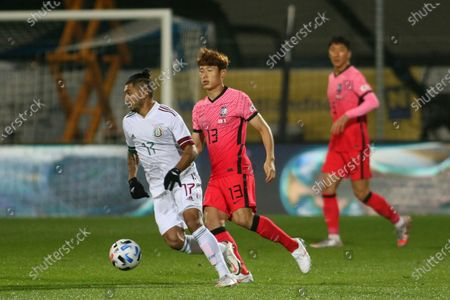 Stock Photo of Mexico's Jesus Corona, left, runs with the ball past South Korea's Son Junho, center, during the international friendly soccer match between Mexico and South Korea at the SC Wiener Neustadt stadium in Wiener Neustadt, Austria
