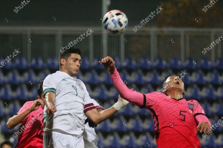 Mexico's Raul Jimenez, left, jumps for the ball with South Korea's Jung Woo young during the international friendly soccer match between Mexico and South Korea at the SC Wiener Neustadt stadium in Wiener Neustadt, Austria