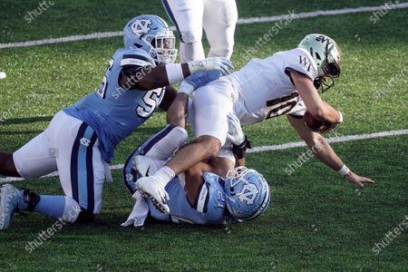 North Carolina defensive lineman Tomari Fox (56) and linebacker Chazz Surratt (21) tackle Wake Forest quarterback Sam Hartman (10) during the second half of an NCAA college football game in Chapel Hill, N.C
