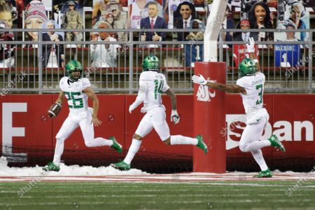 Oregon running back Travis Dye (26) celebrates his touchdown with teammates Kris Hutson (14) and Johnny Johnson III (3) during the second half of the team's NCAA college football game against Washington State in Pullman, Wash., . Oregon won 43-29