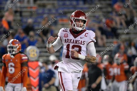 Arkansas quarterback Feleipe Franks (13) celebrates after throwing for a 47-yard touchdown to wide receiver Mike Woods during the first half of an NCAA college football game against Florida, in Gainesville, Fla