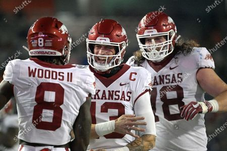 Arkansas quarterback Feleipe Franks (13) celebrates with wide receiver Mike Woods (8) and offensive lineman Dalton Wagner (78) after Franks threw a 47-yard touchdown pass to Woods during the first half of an NCAA college football game, in Gainesville, Fla