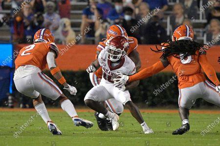 Arkansas wide receiver De'Vion Warren (10) runs after catching a pass between Florida defensive back Brad Stewart Jr. (2), defensive lineman Zachary Carter (17) and defensive back Shawn Davis (6) during the first half of an NCAA college football game, in Gainesville, Fla