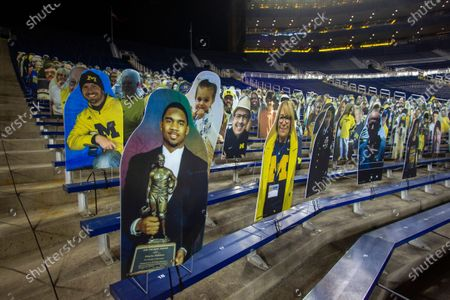 Former Michigan player and Heisman Trophy winner Charles Woodson is featured on one of many cardboard cutouts affixed to Michigan Stadium bleachers, seen before an NCAA college football game in Ann Arbor, Mich