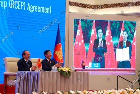 Vietnamese Prime Minister Nguyen Xuan Phuc, left, and Minister of Trade Tran Tuan Anh, right, applaud next to a screen showing Chinese Premier Li Keqiang and Minister of Commerce Zhong Shan holding up signed RCEP agreement, in Hanoi, Veitnam. China and 14 other countries have agreed to set up the world's largest trading bloc, encompassing nearly a third of all economic activity, in a deal many in Asia are hoping will help hasten a recovery from the shocks of the pandemic