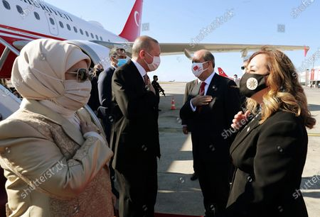 Stock Image of Turkey's President Recep Tayyip Erdogan, left, his wife Emine Erdogan, left, Ersin Tatar, second right, and his wife Sibel Tatar, greet each other during a welcome ceremony at Ercan Airport, in Nicosia, Northern Cyprus, . Erdogan will attend ceremonies celebrating the 37th foundation anniversary of the Northern Turkish Cypriot Republic