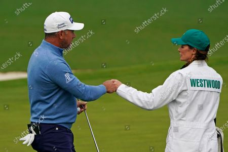 Stock Photo of Lee Westwood, of England, pumps fists with his caddie Helen Storey after a birdie on the second hole during the final round of the Masters golf tournament, in Augusta, Ga