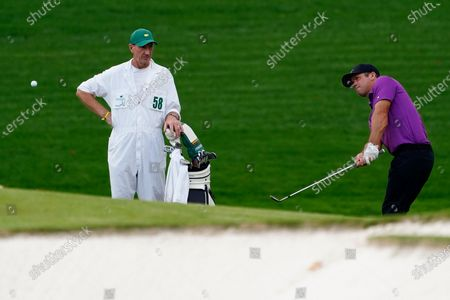 Caddie John McLaren watches as Paul Casey, of England, chips to the 15th hole during the final round of the Masters golf tournament, in Augusta, Ga
