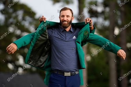 Tiger Woods helps Masters champion Dustin Johnson with his green jacket after his victory at the Masters golf tournament, in Augusta, Ga