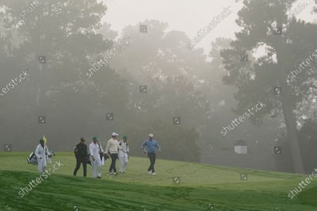 Stock Picture of Matt Wallace, of England, Adam Scott, of Australia, and Lee Westwood, of England, walks down the first fairway during the final round of the Masters golf tournament, in Augusta, Ga