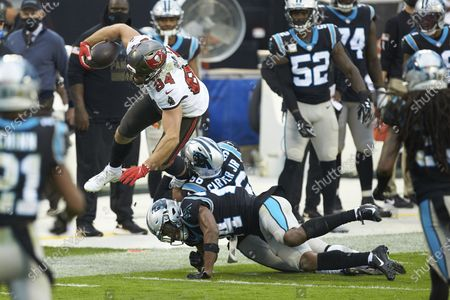 Stock Picture of Tampa Bay Buccaneers tight end Cameron Brate (84) is upended by Carolina Panthers linebacker Jermaine Carter Jr.(56) and cornerback Rasul Douglas (24) during an NFL football game, in Charlotte, N.C