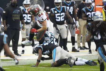 Tampa Bay Buccaneers tight end Cameron Brate (84) is upended by Carolina Panthers linebacker Jermaine Carter Jr.(56) and cornerback Rasul Douglas (24) during an NFL football game, in Charlotte, N.C