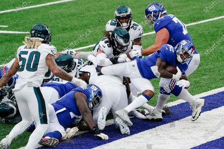 New York Giants running back Wayne Gallman (22) jumps over defenders for a touchdown during the first half of an NFL football game against the Philadelphia Eagles, in East Rutherford, N.J