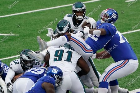Stock Photo of New York Giants running back Wayne Gallman (22) jumps over defenders for a touchdown during the first half of an NFL football game against the Philadelphia Eagles, in East Rutherford, N.J