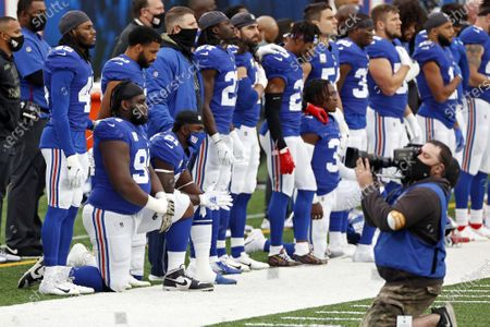 Stock Photo of New York Giants nose tackle Dalvin Tomlinson (94) kneels during the national anthem before an NFL football game against the Philadelphia Eagles, in East Rutherford, N.J