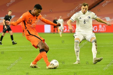 Netherlands' Denzel Dumfries passes the ball to Netherlands' Memphis Depay who scored his side's third goal during the UEFA Nations League soccer match between The Netherlands and Bosnia and Herzegovina at the Johan Cruyff ArenA in Amsterdam, Netherlands, . Right is Bosnia and Herzegovina's Sinisa Sanicanin