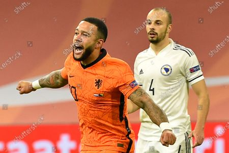 Netherlands' Memphis Depay celebrates scoring his side's third goal during the UEFA Nations League soccer match between The Netherlands and Bosnia and Herzegovina at the Johan Cruyff ArenA in Amsterdam, Netherlands, . Rear is Bosnia and Herzegovina's Darko Todorovic