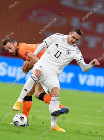 Netherlands' Stefan de Vrij, rear, grabs the arm of Bosnia and Herzegovina's Smail Prevljak during the UEFA Nations League soccer match between The Netherlands and Bosnia and Herzegovina at the Johan Cruyff ArenA in Amsterdam, Netherlands