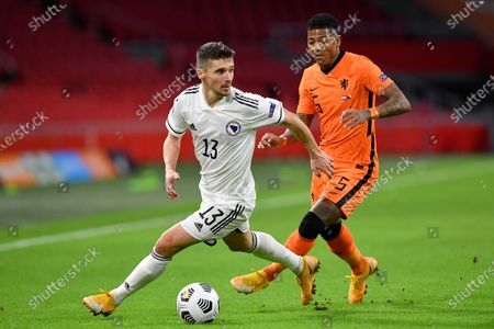 Bosnia and Herzegovina's Gojko Cimirot, left, and Netherlands' Patrick van Aanholt vie for the ball during the UEFA Nations League soccer match between The Netherlands and Bosnia and Herzegovina at the Johan Cruyff ArenA in Amsterdam, Netherlands