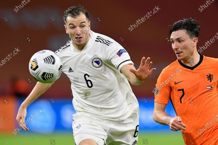 Bosnia and Herzegovina's Sinisa Sanicanin, left, and Netherlands' Steven Berghuis vie for the ball during the UEFA Nations League soccer match between The Netherlands and Bosnia and Herzegovina at the Johan Cruyff ArenA in Amsterdam, Netherlands