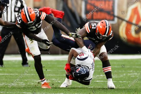 Cleveland Browns linebacker Mack Wilson (51) and Ronnie Harrison (33) tackle Houston Texans wide receiver Randall Cobb (18) during the second half of an NFL football game, in Cleveland