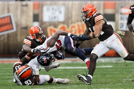 Houston Texans running back Duke Johnson (25) is tackled by Cleveland Browns middle linebacker B.J. Goodson (93), Terrance Mitchell (39) and Sione Takitaki (44) during the second half of an NFL football game, in Cleveland