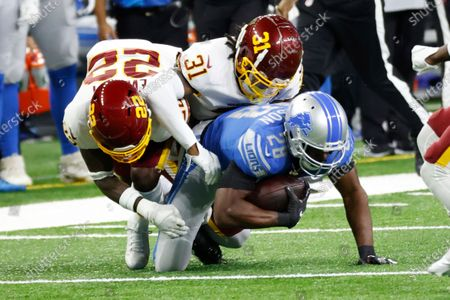 Detroit Lions running back Adrian Peterson (28) is tackled by Washington Football Team safety Deshazor Everett (22) and safety Kamren Curl (31) in the first half during an NFL football game, in Detroit