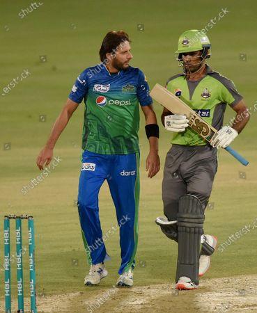Multan Sultans spinner Shahid Afridi, left, chats with Lahore Qalandars batsman Fakhar Zaman during the second eliminator cricket match of Pakistan Super League T20 cup at National Stadium in Karachi, Pakistan