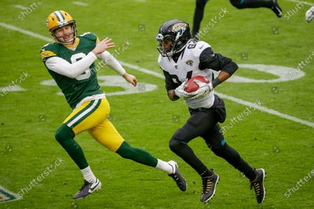 Stock Photo of Green Bay Packers punter J.K. Scott can't stop Jacksonville Jaguars' Keelan Cole as he runs a punt back for a touchdown during the first half of an NFL football game, in Green Bay, Wis