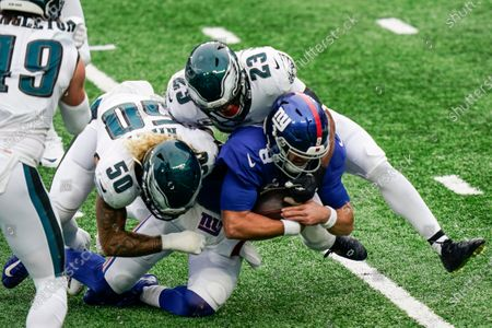 Philadelphia Eagles' Duke Riley (50) and Rodney McLeod (23) tackle New York Giants quarterback Daniel Jones (8) during the first half of an NFL football game, in East Rutherford, N.J
