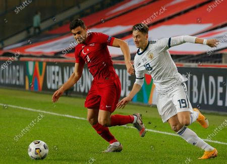 Turkey's Ozan Kabak, left, fights for the ball with Anton Miranchuk, right, during the UEFA Nations League soccer match between Turkey and Russia in Istanbul, . Turkey won the match 3-2
