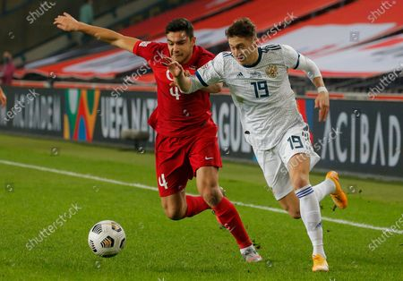 Turkey's Ozan Kabak, left, fights for the ball with Anton Miranchuk, right, during the UEFA Nations League soccer match between Turkey and Russia in Istanbul