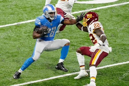 Detroit Lions running back Adrian Peterson (28) attempts to push away Washington Football Team safety Deshazor Everett (22) during the first half of an NFL football game, in Detroit