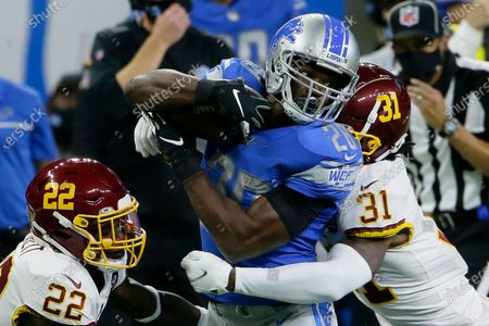 Detroit Lions running back Adrian Peterson (28) is stopped by Washington Football Team safeties Deshazor Everett (22) and Kamren Curl (31) during the first half of an NFL football game, in Detroit