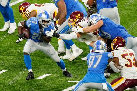 Detroit Lions running back Adrian Peterson (28) avoids Washington Football Team linebacker Cole Holcomb (55) during the second half of an NFL football game, in Detroit