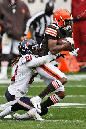 Cleveland Browns wide receiver Rashard Higgins (82) is tackled by Houston Texans cornerback Bradley Roby (21) during the first half of an NFL football game, in Cleveland